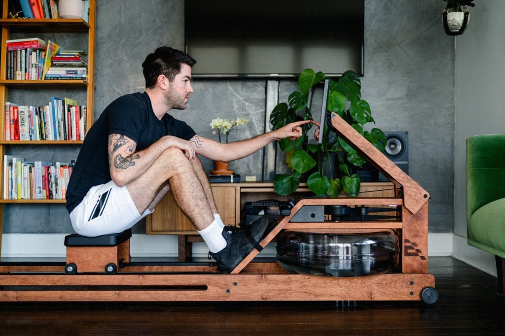 man using touchscreen of rower
